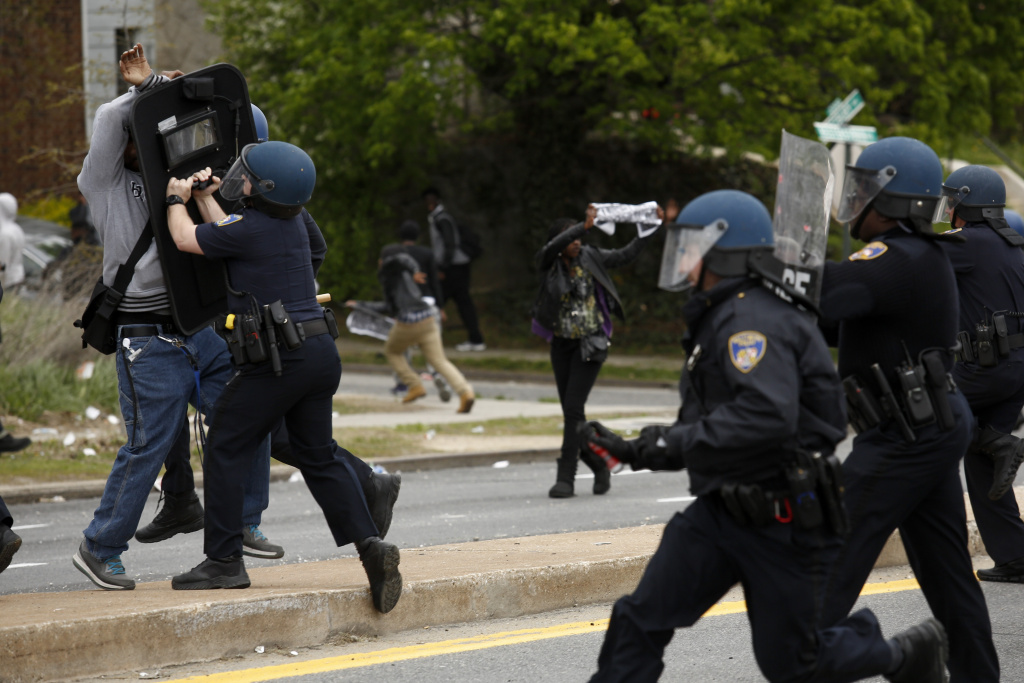 BALTIMORE, MD - APRIL 27: Baltimore Police officers push back a protestor on Reisterstown Road near Mowdamin Mall, April 27, 2015 in Baltimore, Maryland.