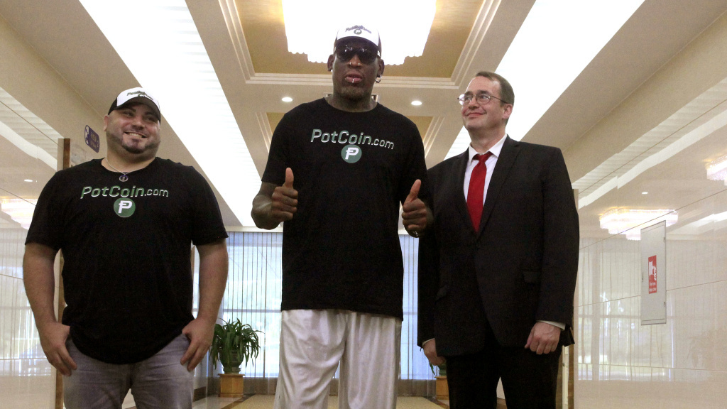 Former NBA basketball star Dennis Rodman, poses with his entourage after arriving at Sunan International Airport in Pyongyang, North Korea, Tuesday. It's Rodman's first visit to North Korea since President Trump took office.