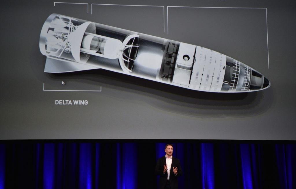 Billionaire entrepreneur and founder of SpaceX Elon Musk speaks in below a computer generated illustration of his new rocket at the 68th International Astronautical Congress 2017 in Adelaide on September 29, 2017.