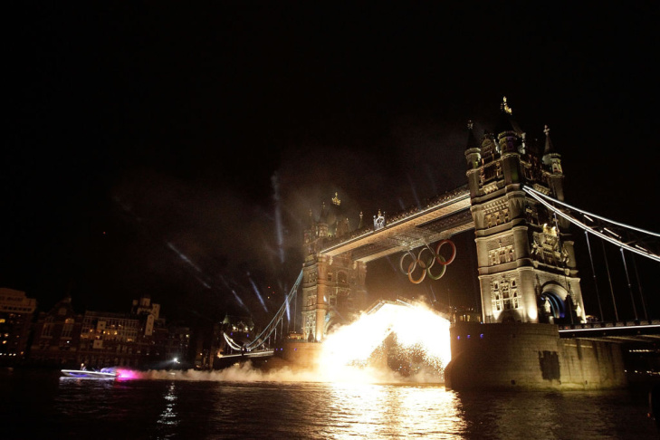 The Tower Bridge is lit with fireworks over the river Thames as the Olympic flame is lit in the Olympic Stadium a few miles away.
