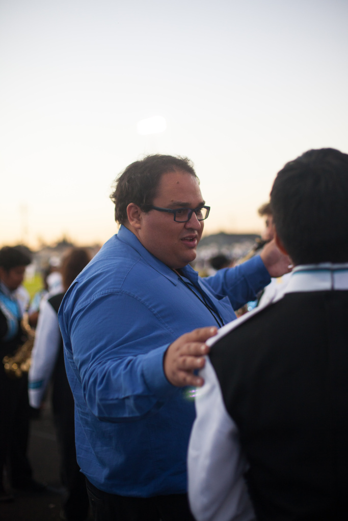 Matthew Stickman, co-director of Locke High School's band, speaks to a student at the homecoming game in October 2017.