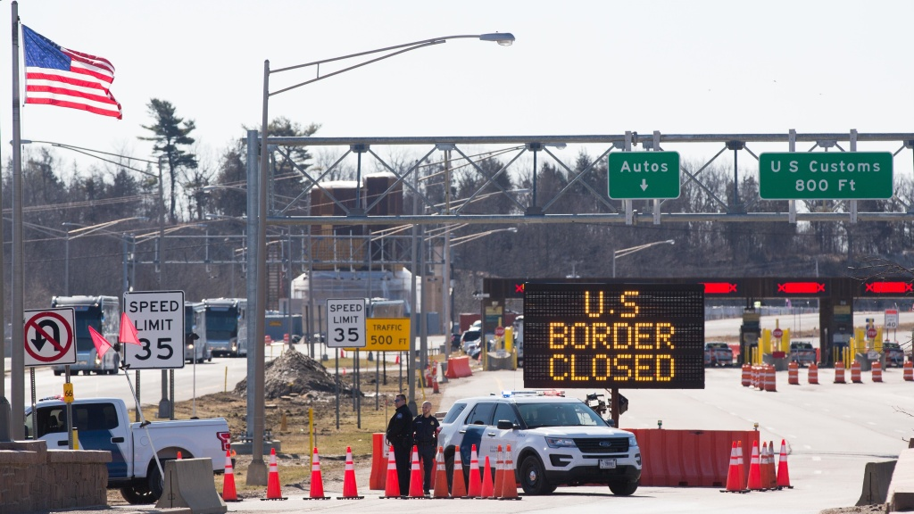 Customs officers stand beside a sign saying the U.S. border is closed in Lansdowne, Ontario, on March 22. The United States agreed with Mexico and Canada to restrict nonessential travel because of the new coronavirus, outbreak.