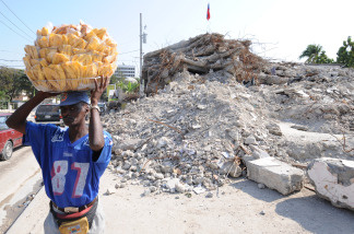 A vendor passes a destroyed building on March 2010 in Port-au-Prince. Two months after Haiti's January 12 earthquake, aids groups were still scrambling Friday to provide for the 1.3 million people left homeless amid growing insecurity in Port-au-Prince.