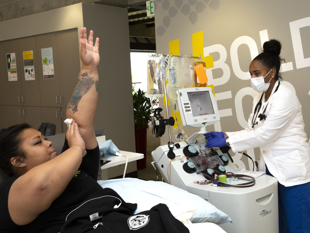 Melissa Cruz elevated her arm after donating COVID-19 convalescent plasma in April 2020, as phlebotomist Jenee Wilson shut down the collection equipment at Bloodworks Northwest in Seattle.