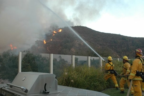 Firefighters battle the flames of the 2007 Santiago Fire in Orange County from the backyard of a home. File photo.