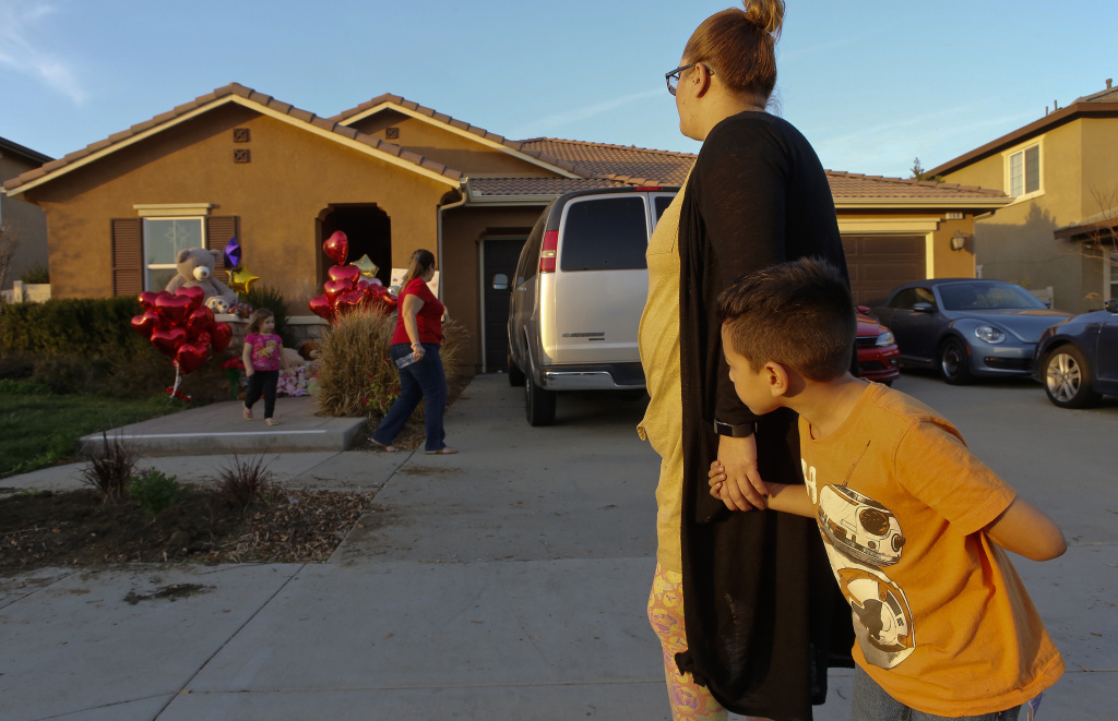 File: Neighbor Avery Sanchez, 6, peeks behinds his mother, Liza Tozier after dropping off his large