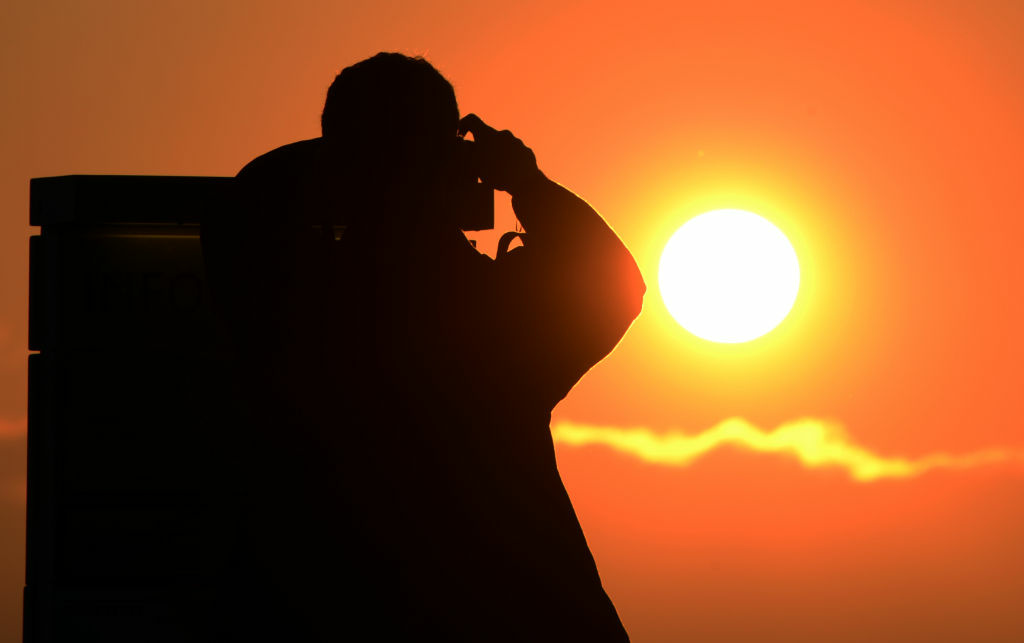 A man prepares to press the shutter on his camera as he takes a picture of the sunset from The Griffith Observatory in Los Angeles, June 4, 2012.