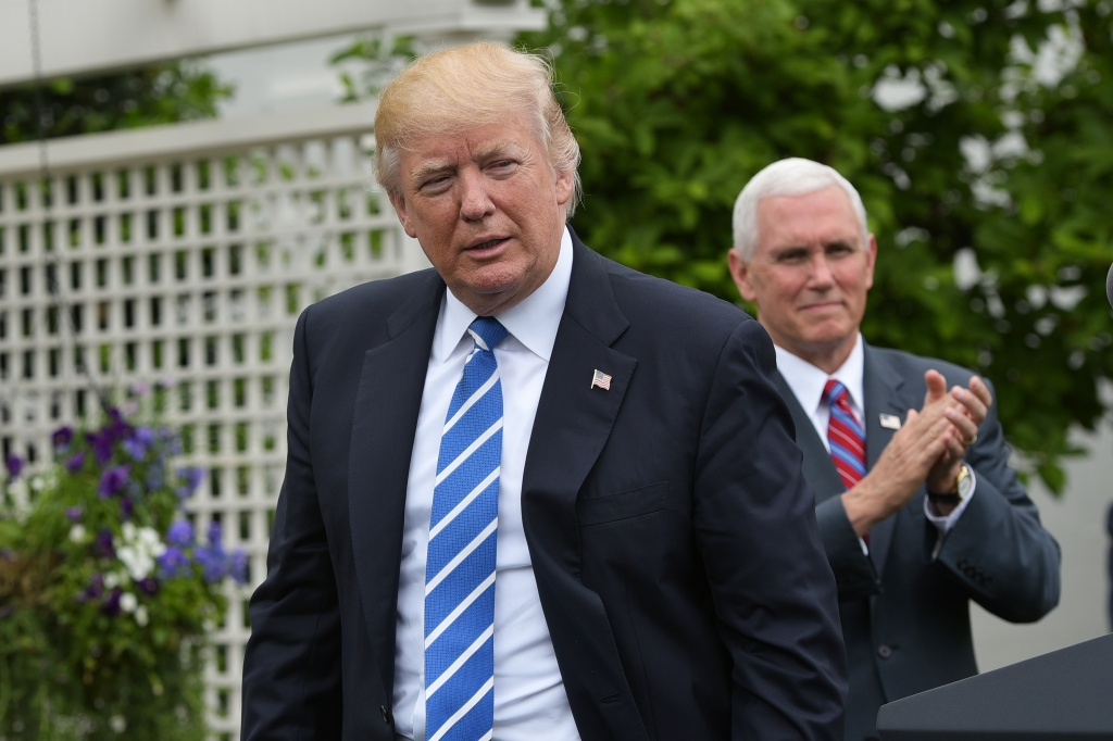 US Vice President Mike Pence (R) applauds US President Donald Trump during an event for the Independent Community Bankers Association.
