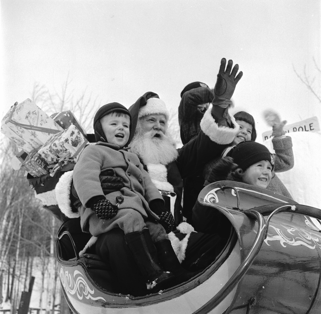 Santa Claus treats young visitors to a sleigh ride at his North Pole Workshop in the Adirondack Mountains of New York State.