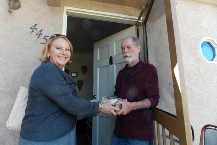 Debbie Case, CEO of Meals on Wheels San Diego County, delivers lunch and dinner to 75-year-old Dave Kelly. Kelly lost his sight about two years ago and reluctantly gave up cooking.