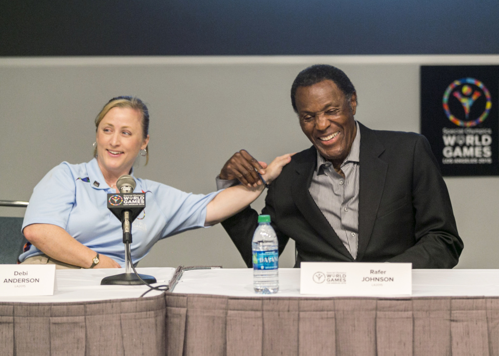 Debi Anderson, LA2015 Board Member and Special Olympics Athlete, left, jokes with Olympic Gold medalist Rafer Johnson, as he recalls the first Special Olympics World Games he attended during a news conference in Los Angeles Monday, July 20, 2015.