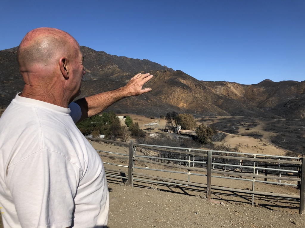 Butch Humphrey explains how the fire came over the ridge and toward his house.