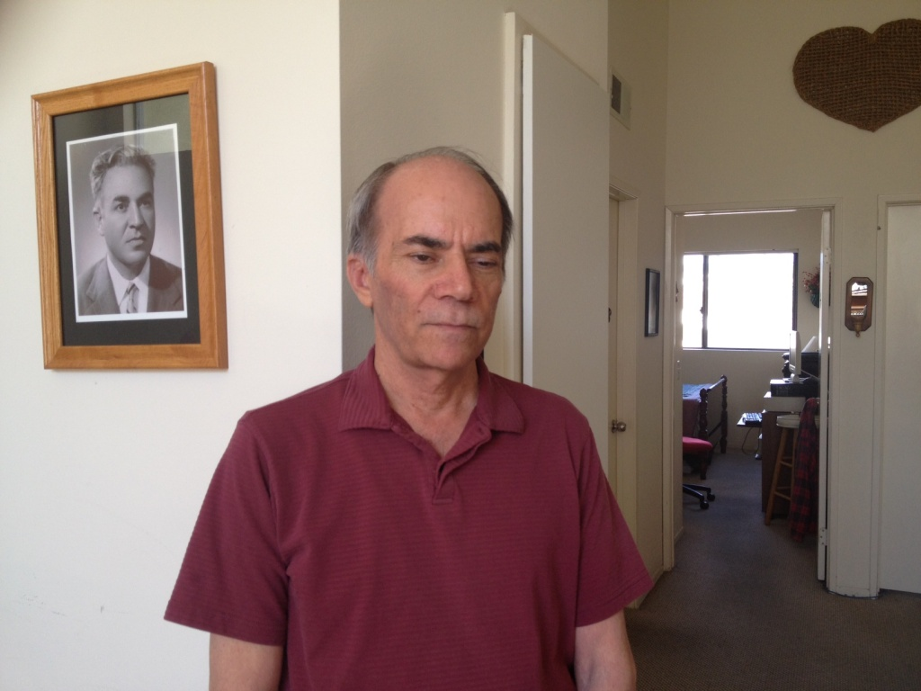 Iranian poet Majid Naficy stands next to an old photograph of his father, inside his Los Angeles apartment.