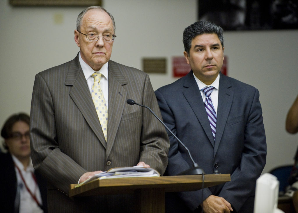 James Riddet, left, attorney for Santa Ana City Councilman Carlos Bustamante, right, stand in Orange County Superior Court in Santa Ana, during Bustamante's arraignment on sexual assault charges involving seven women. Orange County's CEO resigned Thursday for his handling of the allegations.