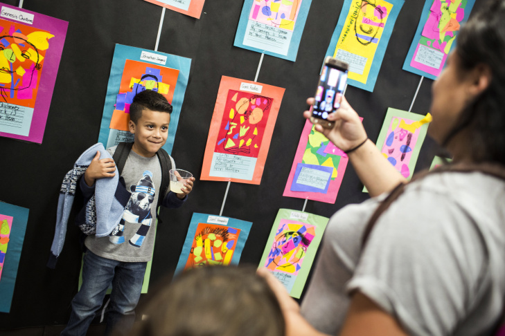 Students pose for pictures in front of their self-portraits during an art show at Florence Griffith Joyner Elementary School in Watts on Tuesday afternoon, Oct. 11, 2016. The school is one of the new schools in the Turnaround Arts program, a White House initiative taking failing schools and working to improve them through the arts.
