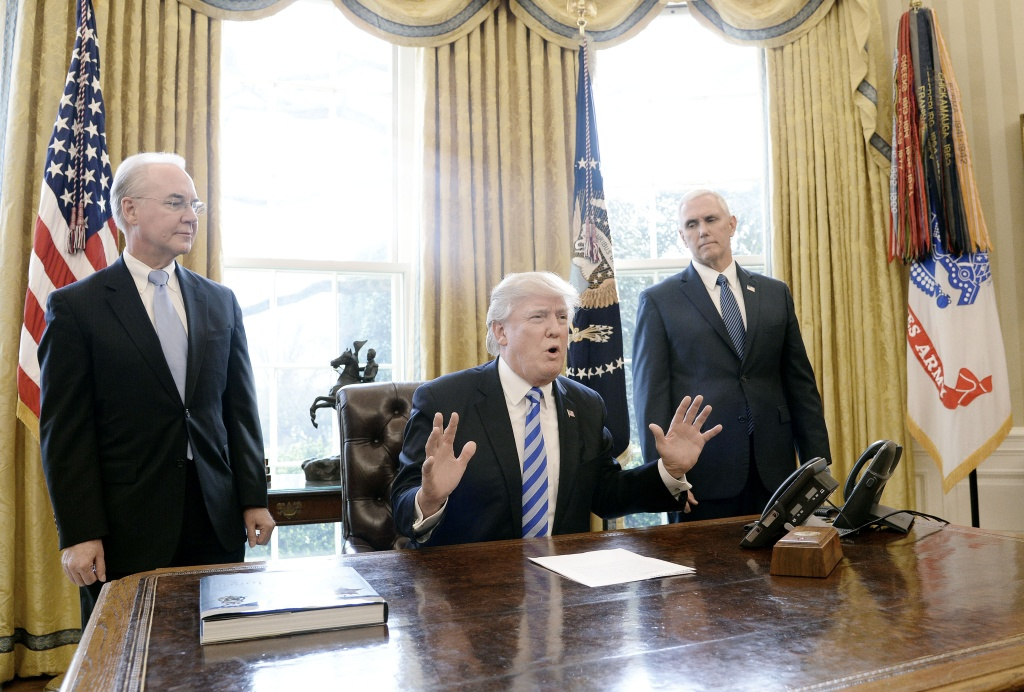 U.S. President Donald Trump reacts with HHS Secretary Tom Price (L) and Vice President Mike Pence (R) after Republicans abruptly pulled their health care bill from the House floor.