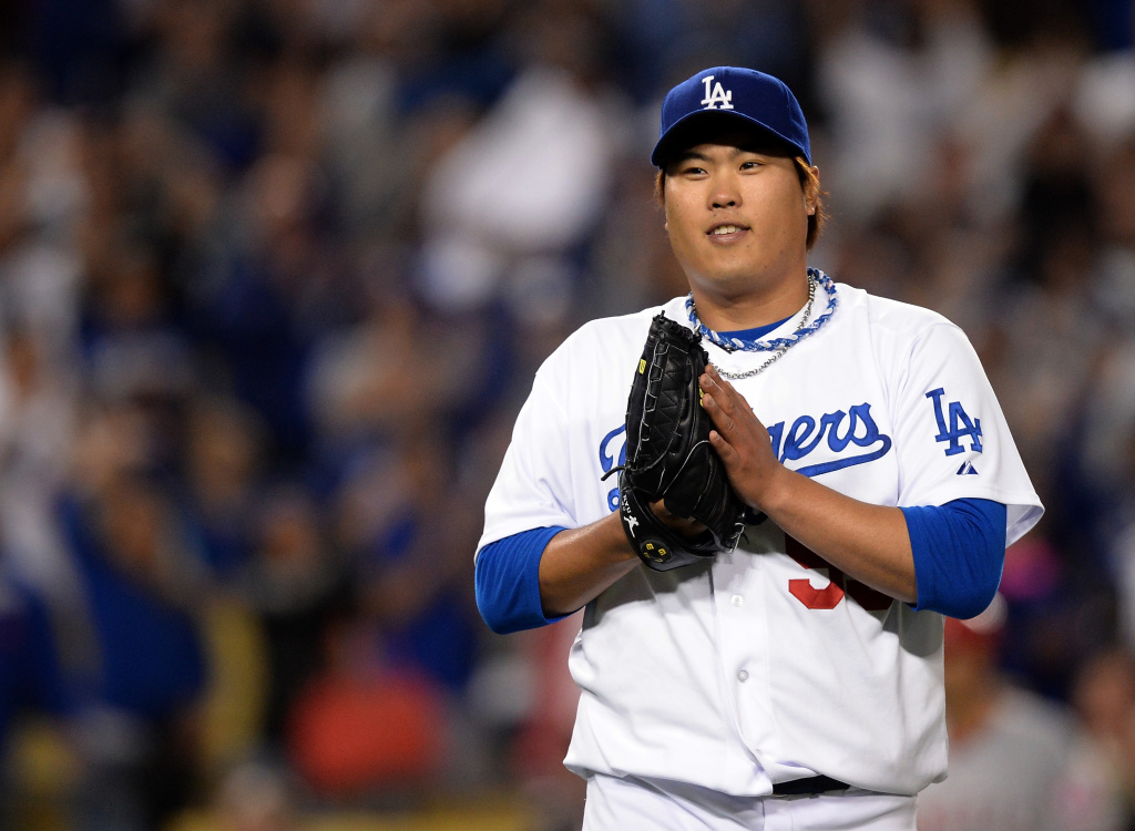 Hyun-Jin Ryu #99 of the Los Angeles Dodgers reacts to his two hit complete game shutout of the Los Angeles Angels with A.J. Ellis #17 at Dodger Stadium on May 28, 2013 in Los Angeles, California.