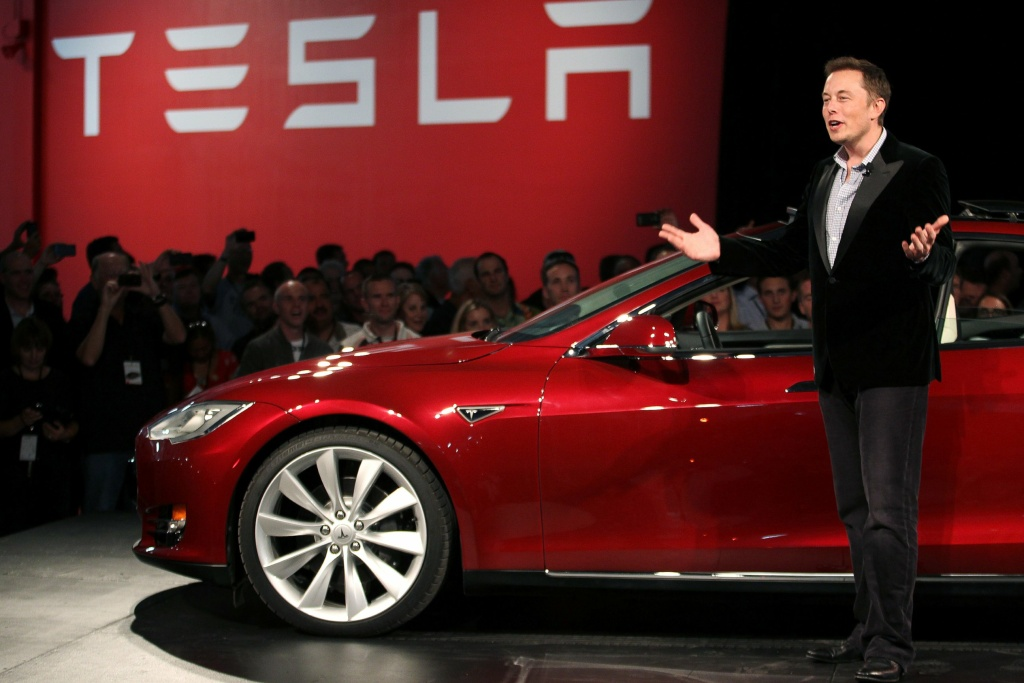 Tesla's Elon Musk standing near his Model S. Steve Levine says Musk is absolutely winning the war for the electric car.