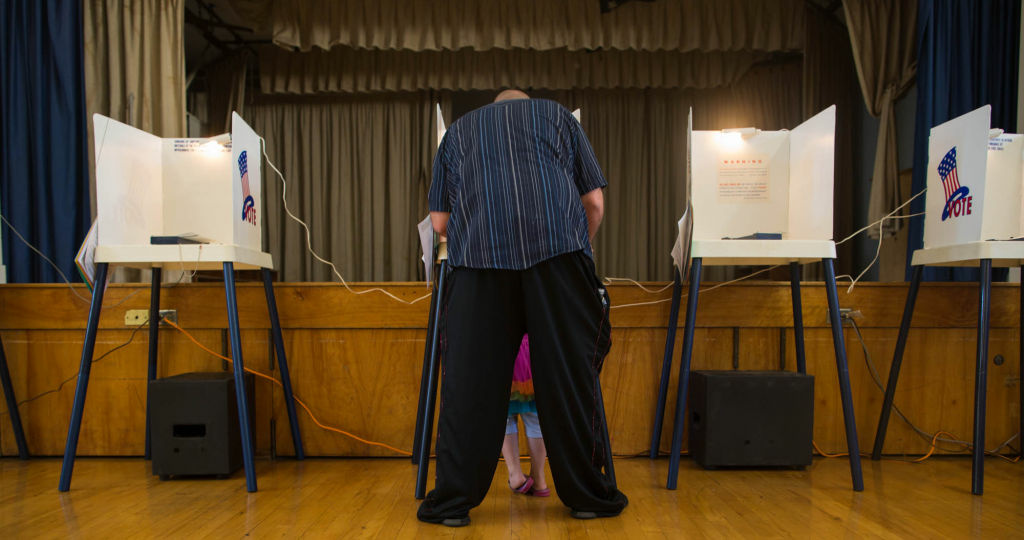 Matt Caudillo casts his vote while his daughter looks on at Yorkdale Elementary School in Highland Park on November 6, 2012