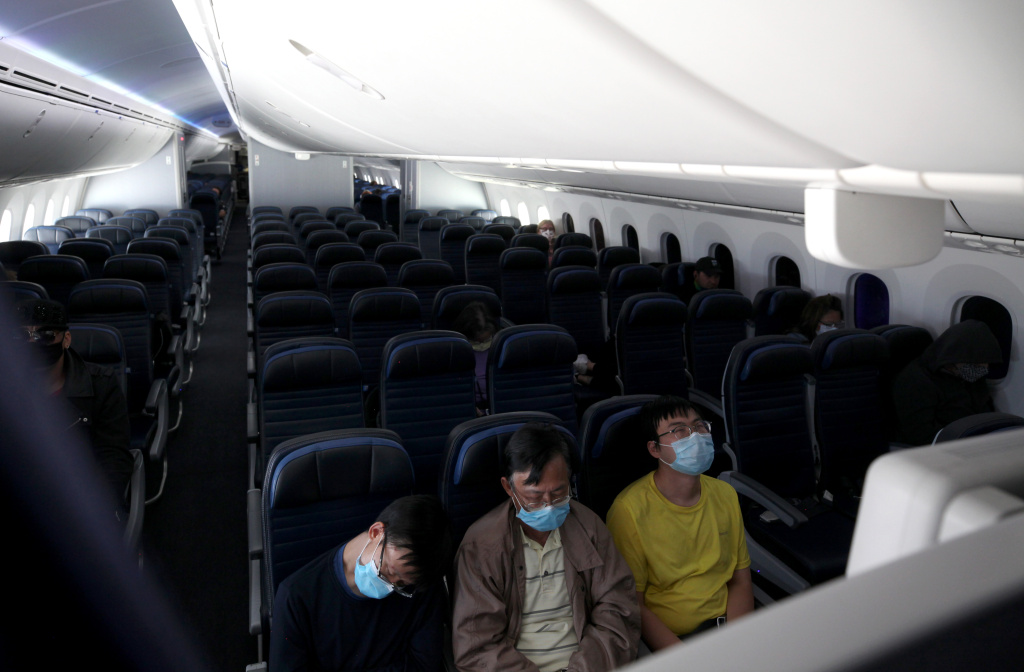 Passengers sleep while flying on a United Airlines flight on route to Houston, Texas.