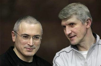 Mikhail Khodorkovsky, left, and his co-defendant Platon Lebedev, right, talk behind a glass enclosure at a court room in Moscow, Russia, Thursday, Dec. 30, 2010.