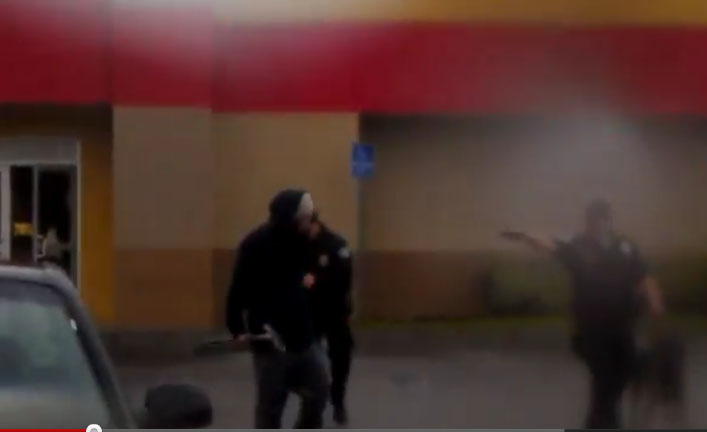A suspect carrying a long metal object approaches police on Monday at a Carl's Jr. in Monterey Park, CA.