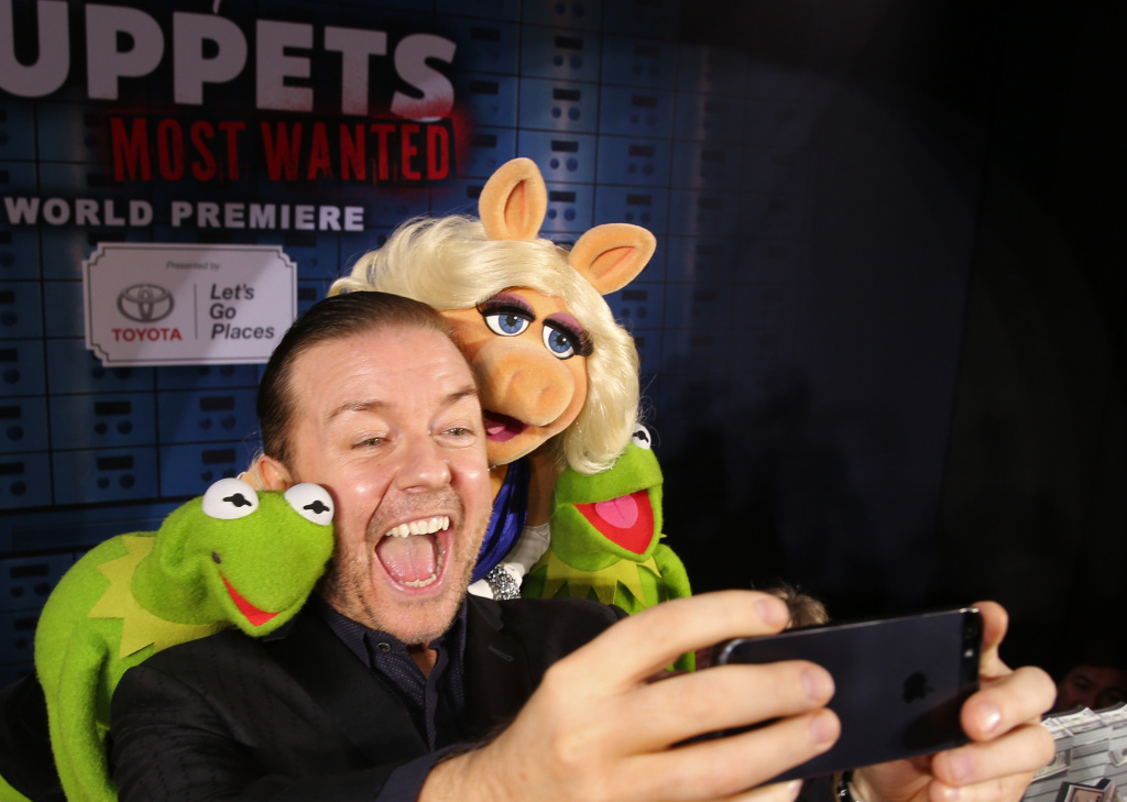 (L-R) Constantine, actor Ricky Gervais, Miss Piggy and Kermit the Frog arrive at the world premiere of Disney's