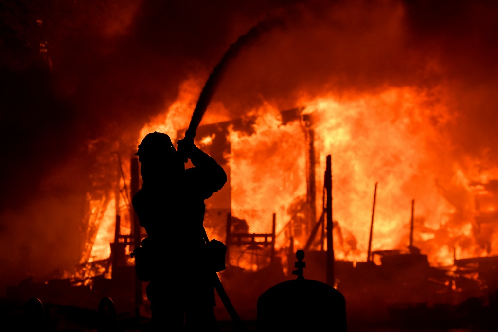 In this file photo, a firefighter douses flames as a home burns in the Napa wine region of California on October 9, 2017, as multiple wind-driven fires whipped through the region. The Legislative Analyst's Office said state agencies spent $1.5 billion fighting fires and recovery in the North Bay in October, including debris removal and infrastructure repair.