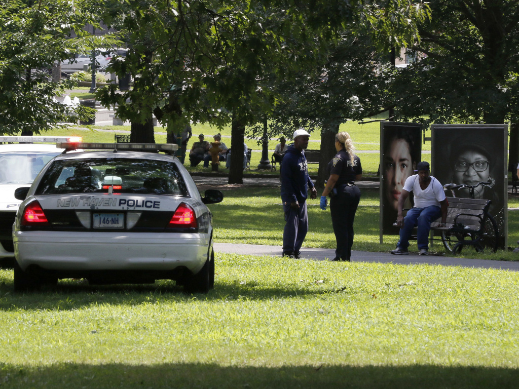 A police officer speaks to a man walking on New Haven Green, Wednesday, Aug. 15, in New Haven, Conn. More than a 100 people fell ill from suspected drug overdoses linked to a batch of synthetic marijuana laced with fubinaca.