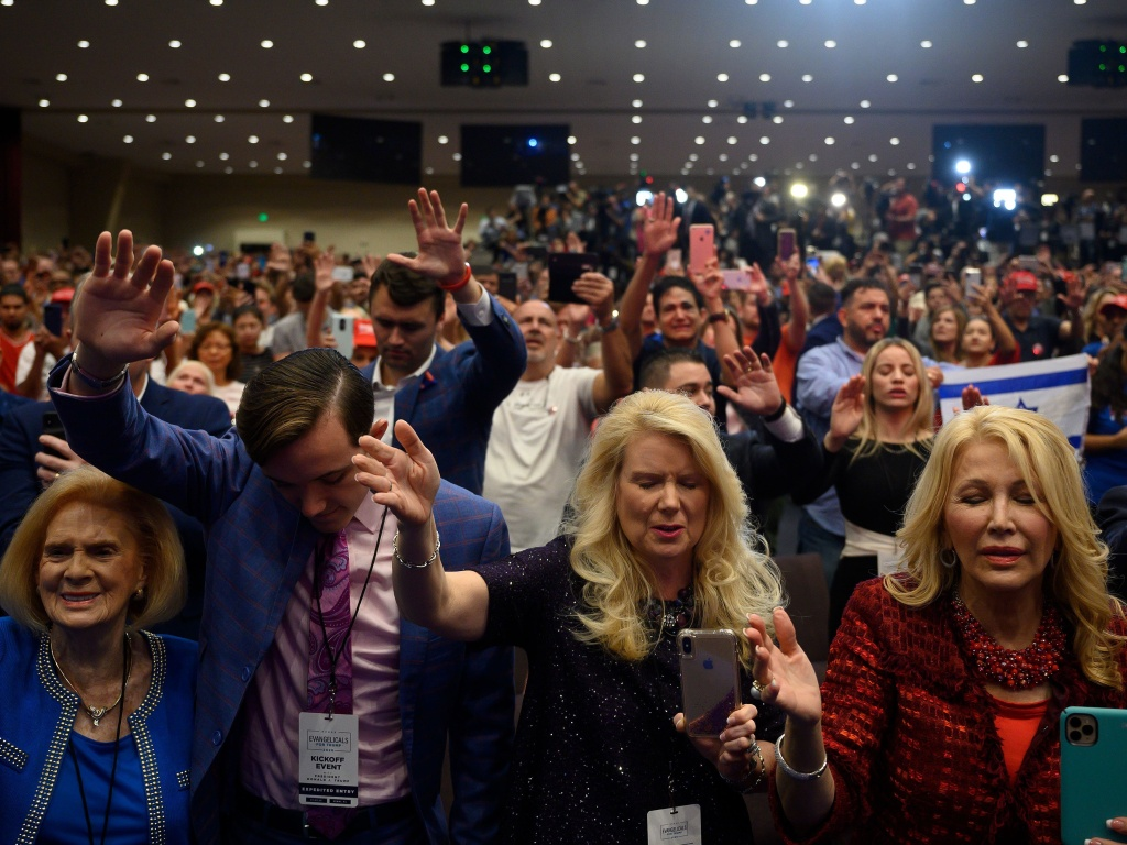 Supporters pray as President Donald Trump speaks during an