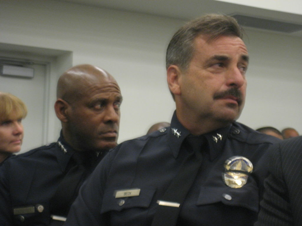 LAPD deputy chiefs Charlie Beck (right) and Earl Paysinger listen to residents speak about the qualities they want to see in a new chief at a Police Commission meeting. Beck, Paysinger, and Deputy Chief Sandy Jo MacArthur (far left) are all seeking to succeed Chief Bill Bratton.