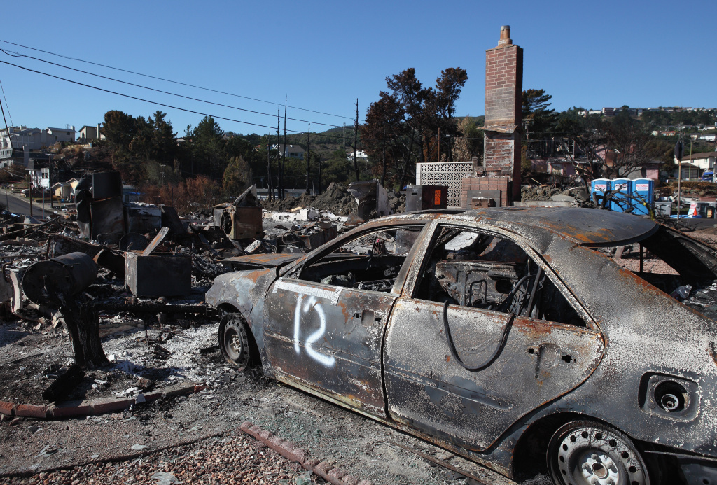 The shell of a car sits in the driveway of a burned home near the epicenter of the gas line explosion that devastated a neighborhood near San Francisco International Airport September 24, 2010 in San Bruno, California.