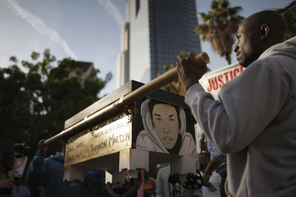 People lift a box containing letters to be delivered to U.S. Attorney General Eric Holder during a rally to demand justice for the shooting of Trayvon Martin in Los Angeles, California.