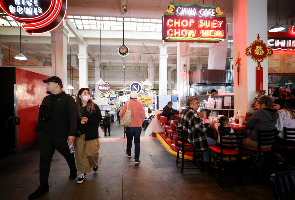A woman walks while wearing a face mask as patrons sit at a restaurant in Grand Central Market in Los Angeles, California.