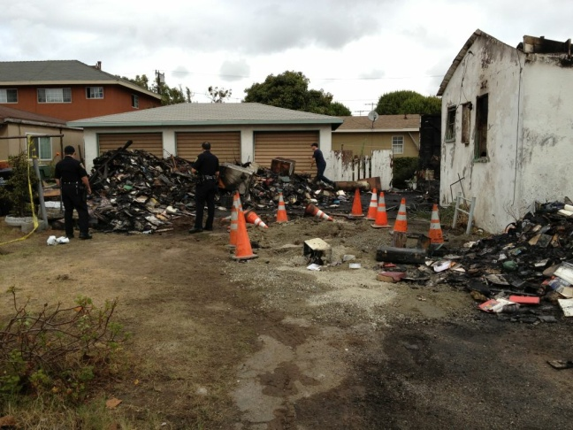 Police officers circle some of the charred debris retrieved from the suspect's burning house.