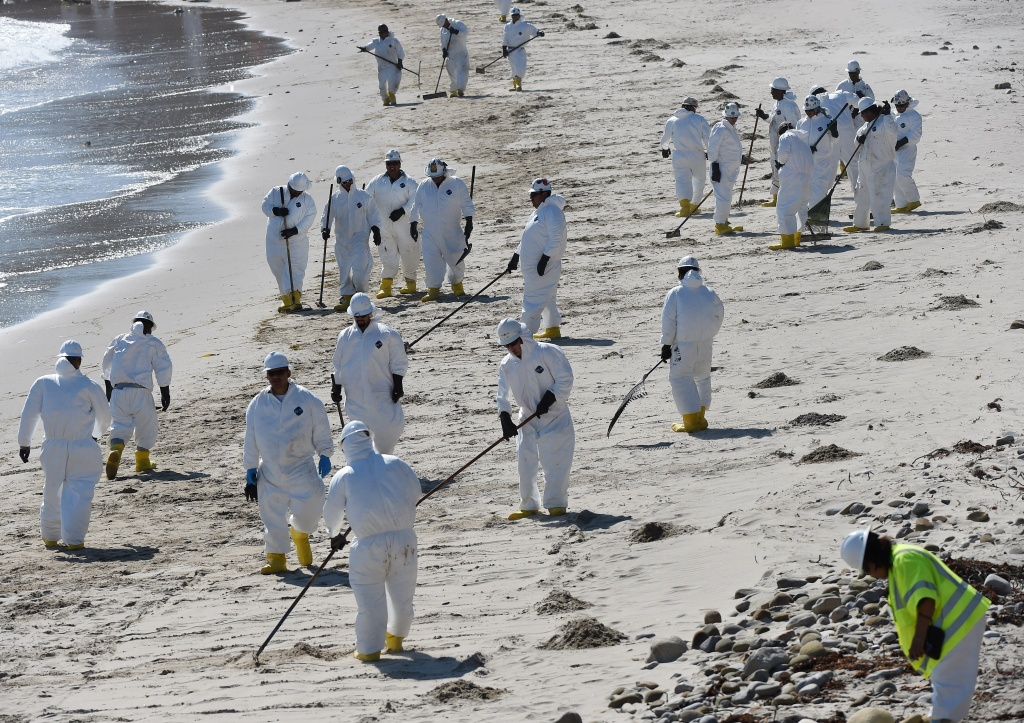 Workers clean oil from the rocks and beach near Refugio State Beach in Goleta, California, May 22, 2015. The oil company behind a crude spill on the California coast, Plains All American Pipeline, said Tuesday it had been indicted on 46 counts related to the spill.