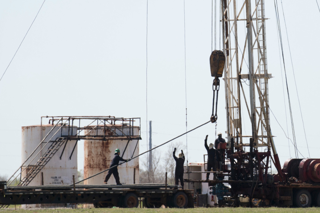 Workers pull pipes from an oil well in 2016 near Crescent, Okla. The oil industry wants to attract a new, more diverse generation of workers, but a history of racism and sexism makes that difficult.
