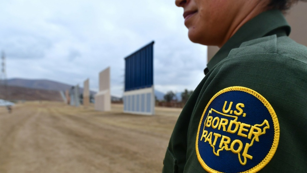 A U.S. Border Patrol officer stands near prototypes of President Donald Trump's proposed border wall on Nov. 1, 2017, in San Diego.
