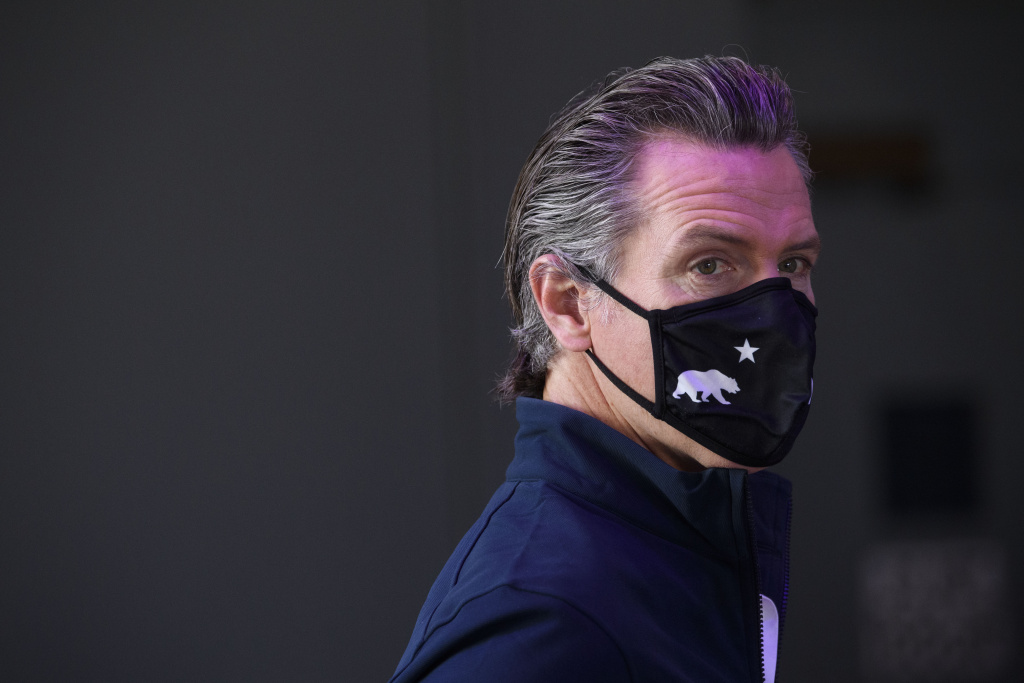 California Governor Gavin Newsom wears a face mask as he prepares to give a briefing after touring a Covid-19 vaccination site on February 22, 2021 in Long Beach, California.