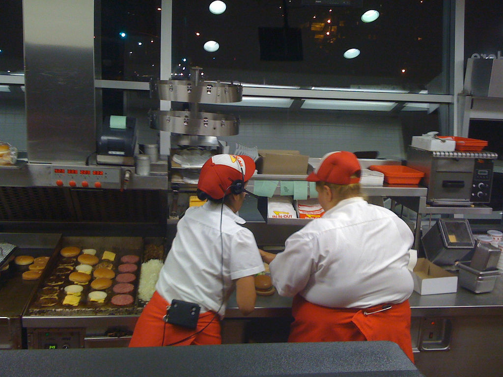 In N Out employees cooking up burgers on the grill at the Westwood location.