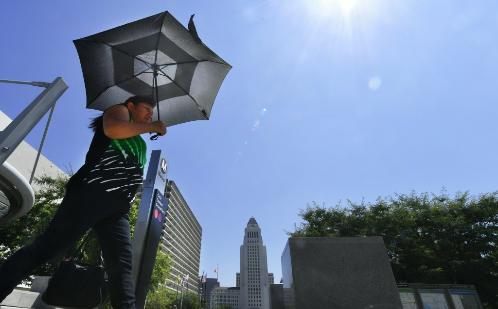 A pedestrian uses an umbrella while walking past City Hall in Los Angeles amid an ongoing heatwave on Aug. 29, 2017, generating triple-digit temperatures in some southern California communities.