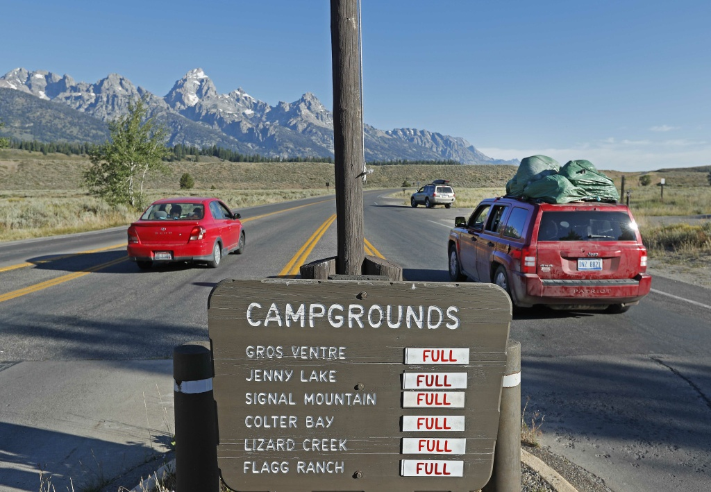 With a sign showing full camp grounds, cars drive into Grand Teton National Park on August 19, 2017 outside Jackson, Wyoming.