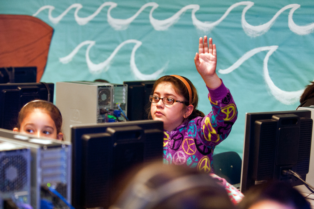 Third grader Natalia Gonzalez raises her hand as students take quizzes during a computer lab session.