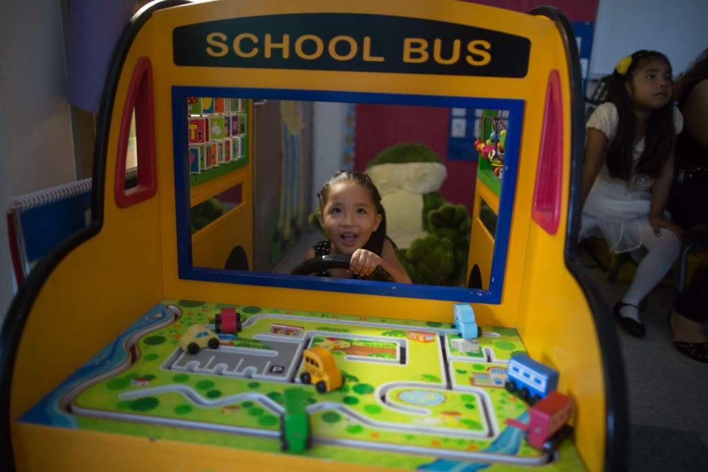 The younger sibling of a graduating student plays in a Transitional Kindergarten classroom's toy school bus at Stanley Mosk elementary school in Winnetka.