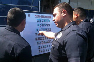 LAPD officer Manuel Gomez and others look at poster of Pueblo Bishops Bloods after a sweep operation.