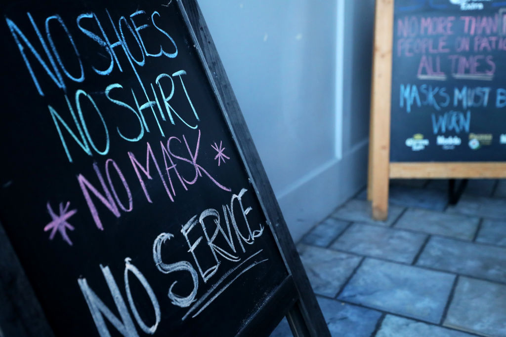 A sign requiring a face mask at SpeakEasy Bar & Grill on May 09, 2020 in Newport, Rhode Island.