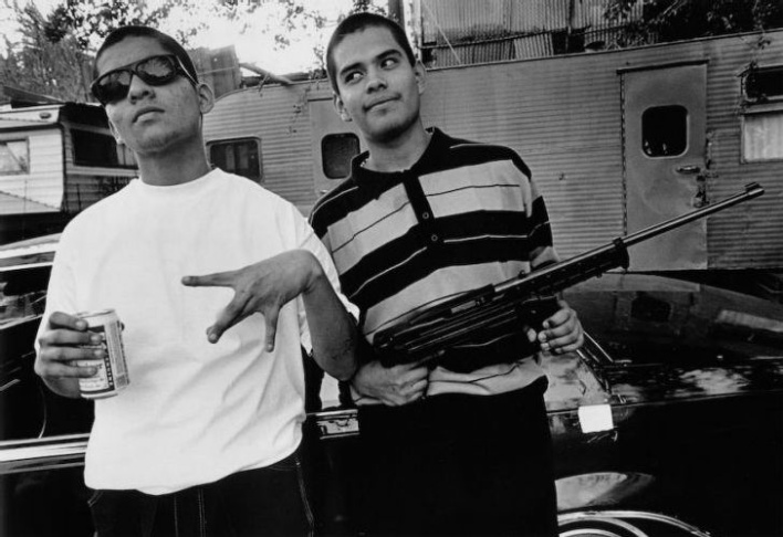 Two homeboys holding a .22 semi-automatic rifle in East Los Angeles, 1992. The teenager on the right is now dead.