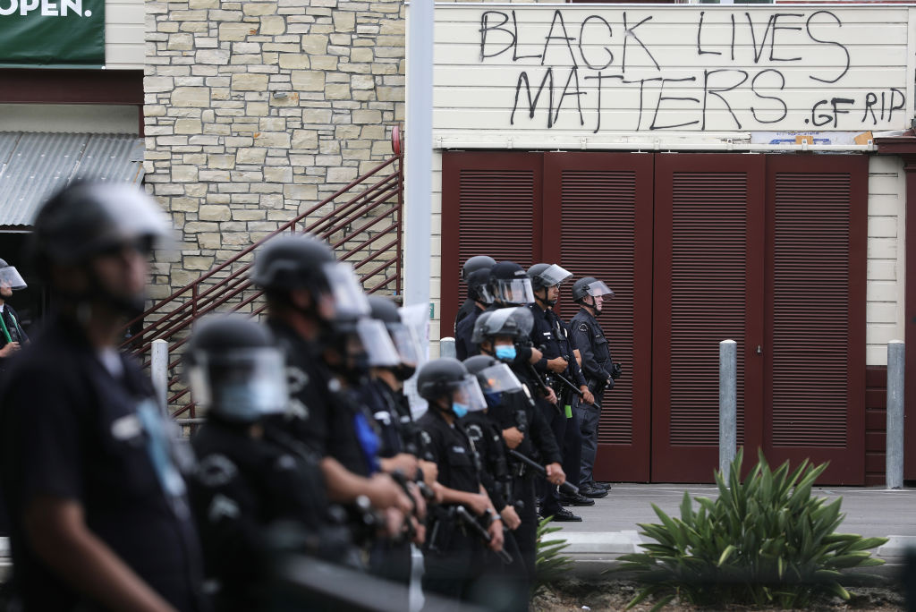 LAPD officers keep watch beneath graffiti reading 'Black Lives Matters' during demonstrations following the death of George Floyd on May 30, 2020 in Los Angeles, California.