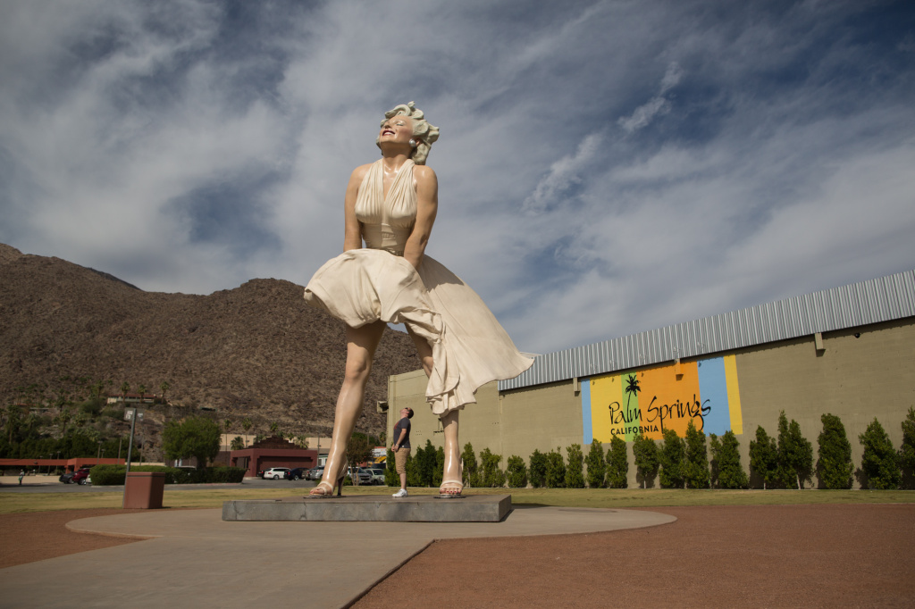 A tourist looks up the skirt of a massive Marilyn Monroe statue in downtown Palm Springs, Calif.