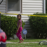 A young neighbor watches as police respond to a double homicide in Flint, Mich., on June 30, 2013. The alleged assailant was 13.